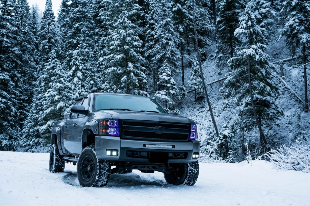 gray pickup truck on snow field surrounded by trees